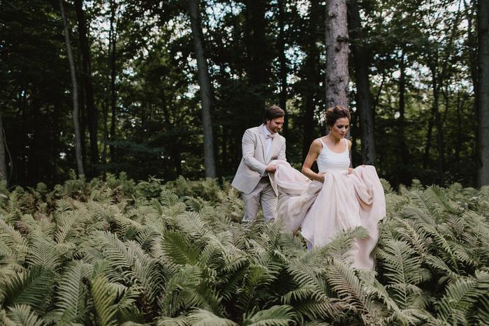 groom holding bride's dress as the walk