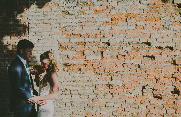 bride and groom portrait against brick wall
