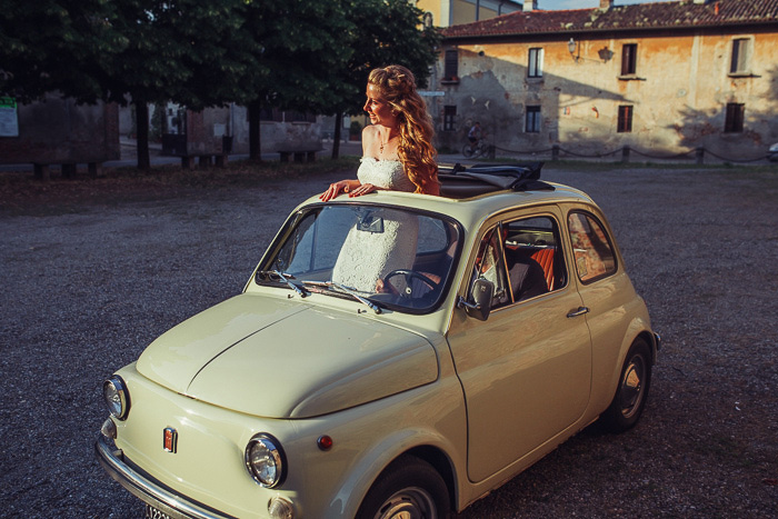 bride standing through sun roof of tiny italian car