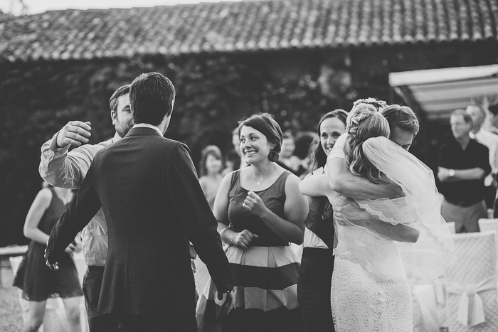 bride and groom hugging guests