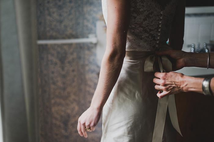 bride getting sash tied