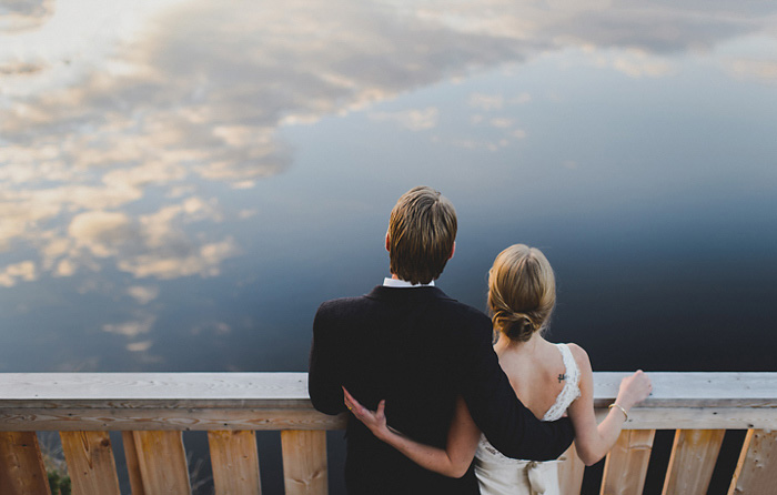 bride and groom looking out on the lake