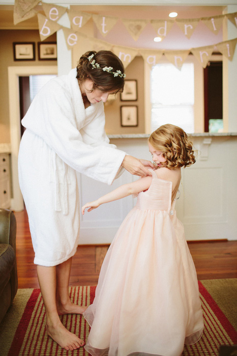 bride helping flower girl get dressed