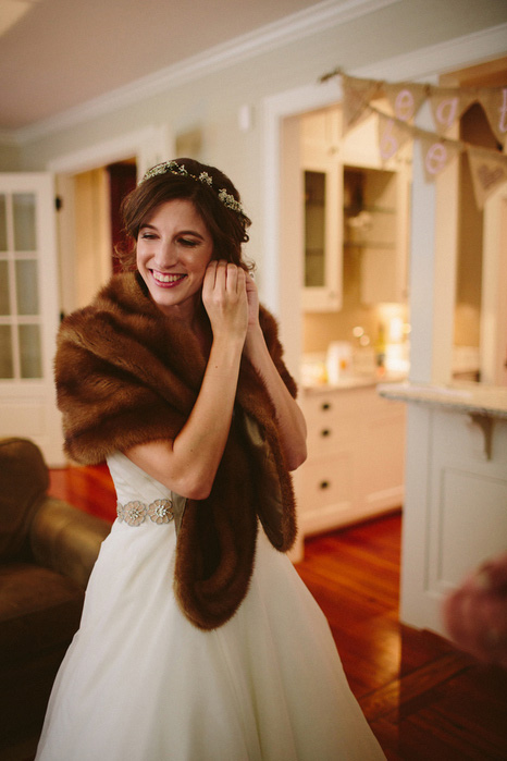 bride in fur stole putting on earrings