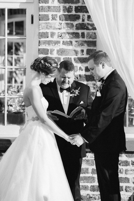 bride and groom with heads bowed at wedding ceremony