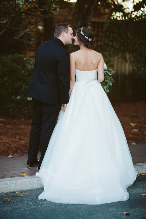 bride and groom kissing on street