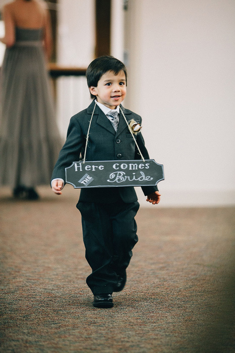 ring bearer wearing here comes the bride sign