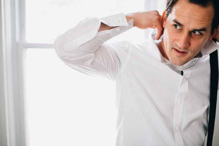 groom adusting shirt