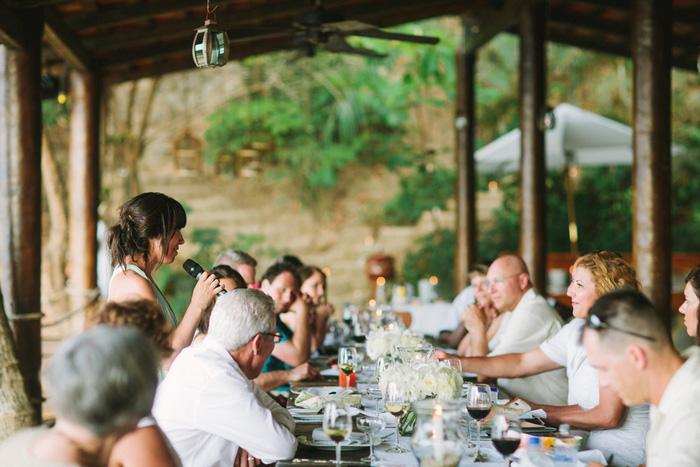 wedding guests at reception dinner on resort porch