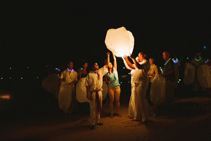 lighting a wish lantern on the beach