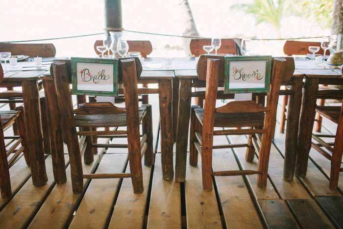 bride and groom signs on backs of chairs