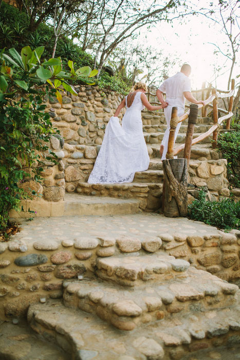 bride and groom climbing stone stairs