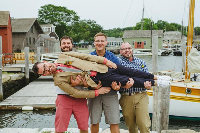 groomsmen holding groom