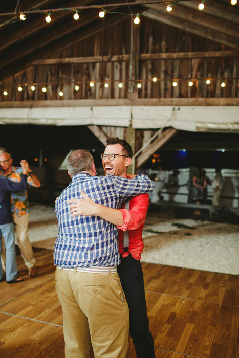groom hugging guest on dance floor