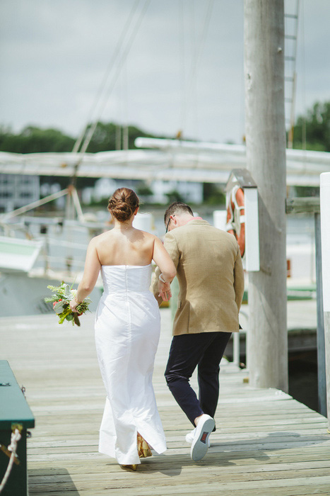 bride and groom walking on dock