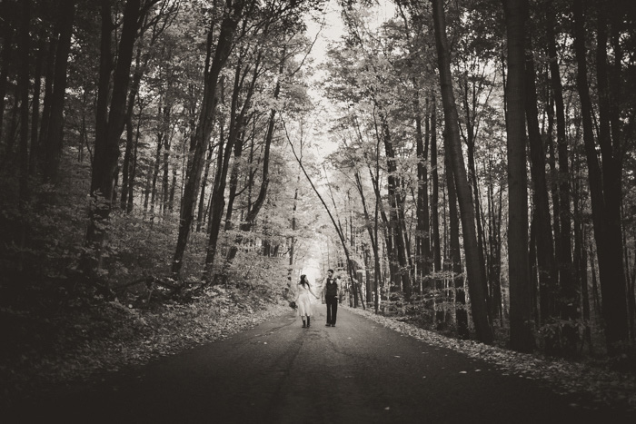 bride and groom walking down wooded road