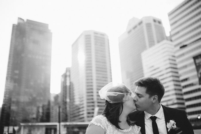 bride and groom kissing in front of cityscape