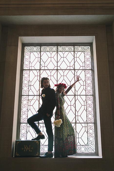 Bride and groom standing inside City Hall window