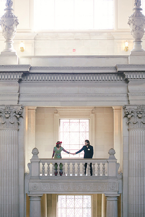 bride and groom hoding hands on second level of San Francisco City Hall