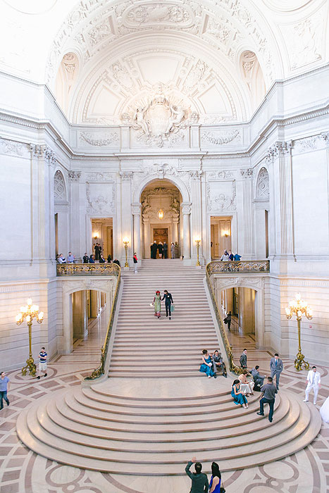 bride and groom walking down city hall stairs
