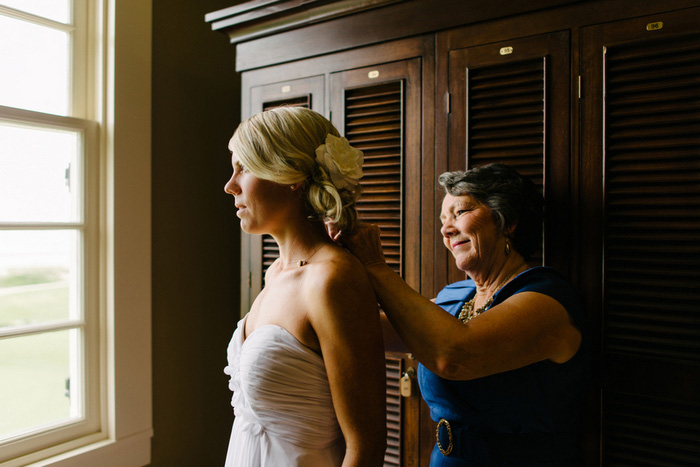 mother of the bride putting bride's necklace on her