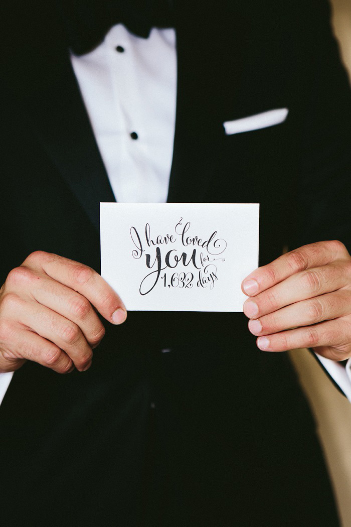 groom holding card