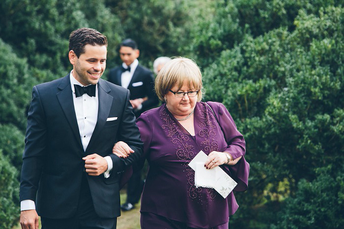 groom walking down aisle with his mother