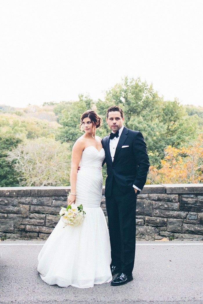 bride and groom portrait in front of stone wall