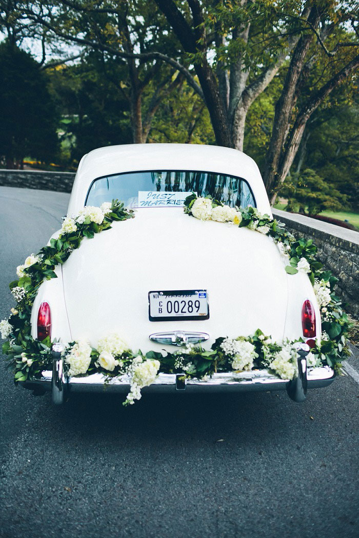vintage wedding car with floral garland