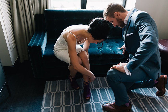 groom helping bride with her shoes
