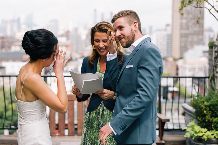 bride and groom wiping away tears during ceremony