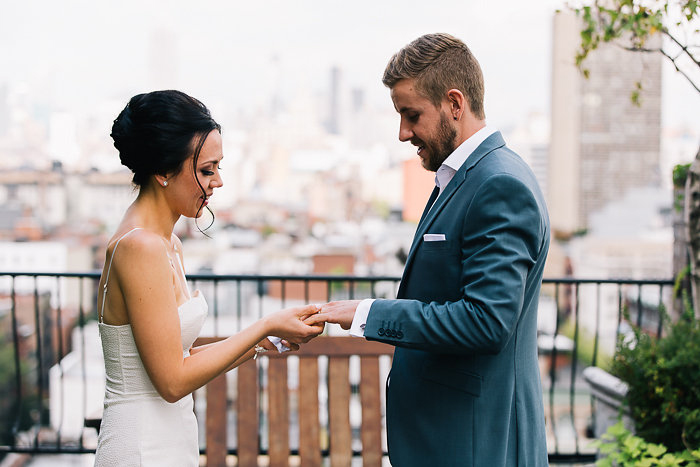 bride placing ring on groom's finger