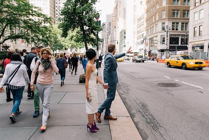 bride and groom hailing a cab