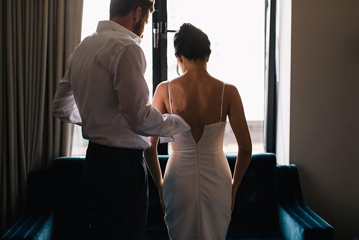 groom zipping up bride's dress