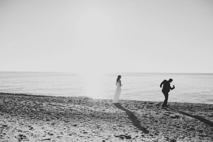 bride and groom skipping rocks on the beach