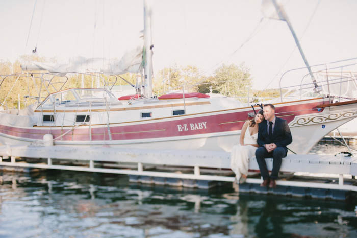 bride and groom sitting on the dock