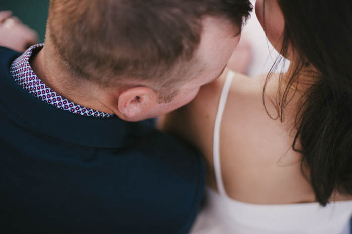 groom kissing bride's shoulder