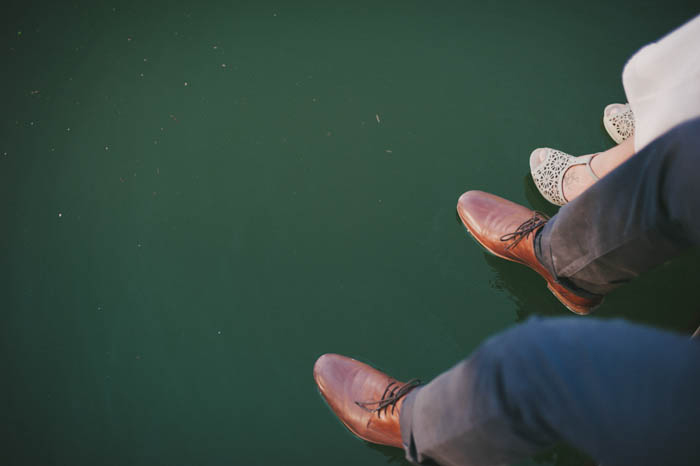 bride and groom's feet hanging off the dock