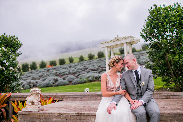 bride and groom sitting on stone wall