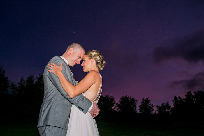 bride and groom portrait against purple sky