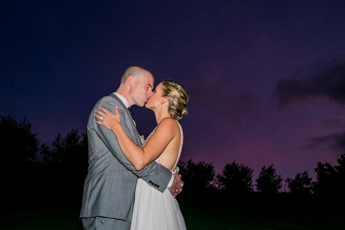bride and groom kissing under Maui sky