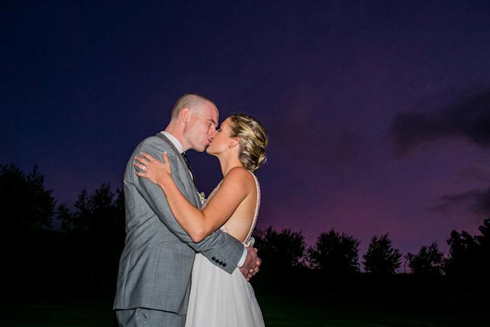 bride and groom kissing under Maui sky