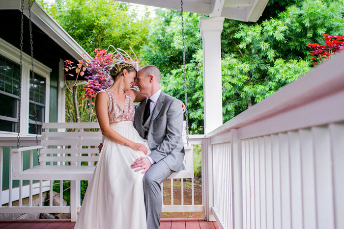 bride and groom sitting on porch swing