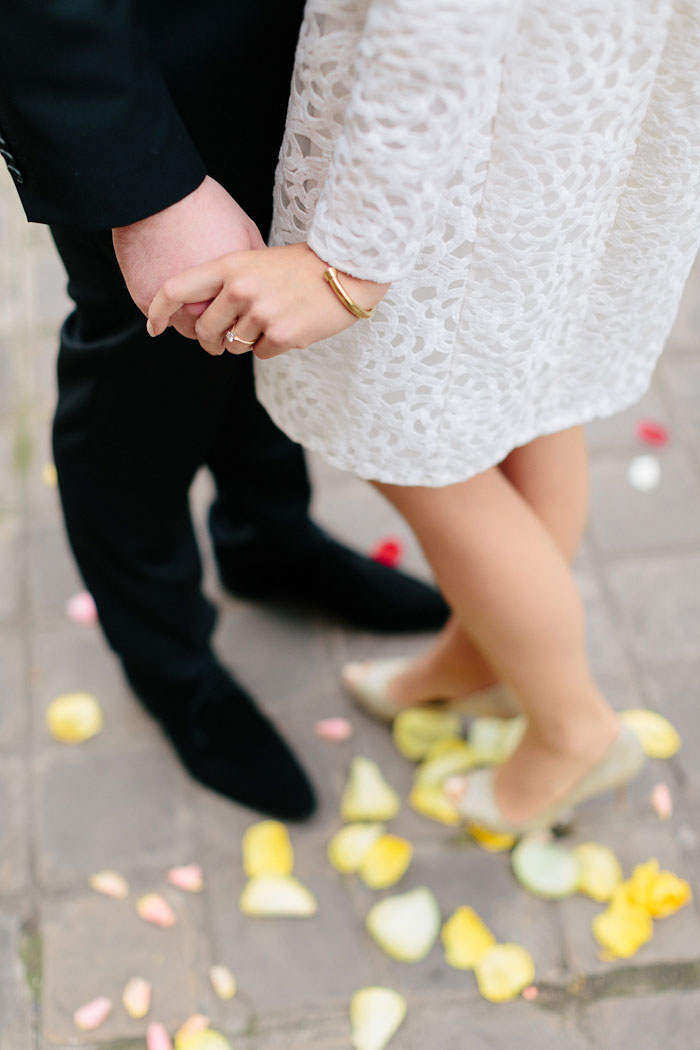 bride and groom standing on yellow rose petals
