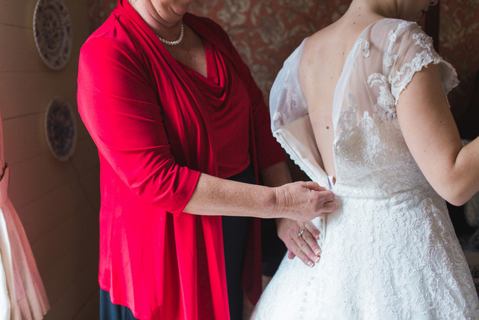 bride having dress zipped up