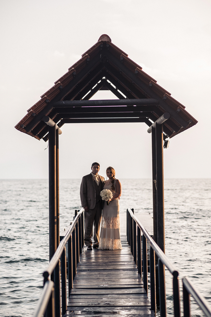 bride and groom on lake pier