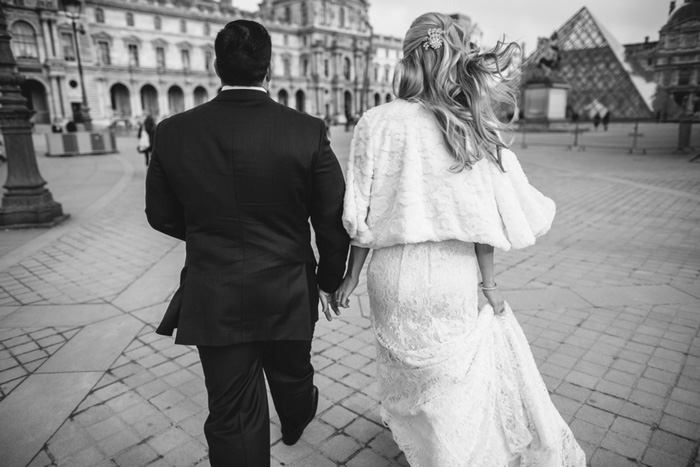 bride and groom walking to the louvre