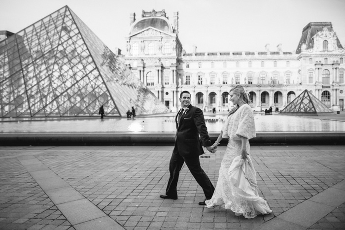 bride and groom walking by the Louvre