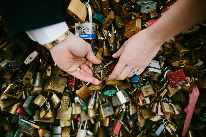 bride and groom putting lock on locks of love bridge