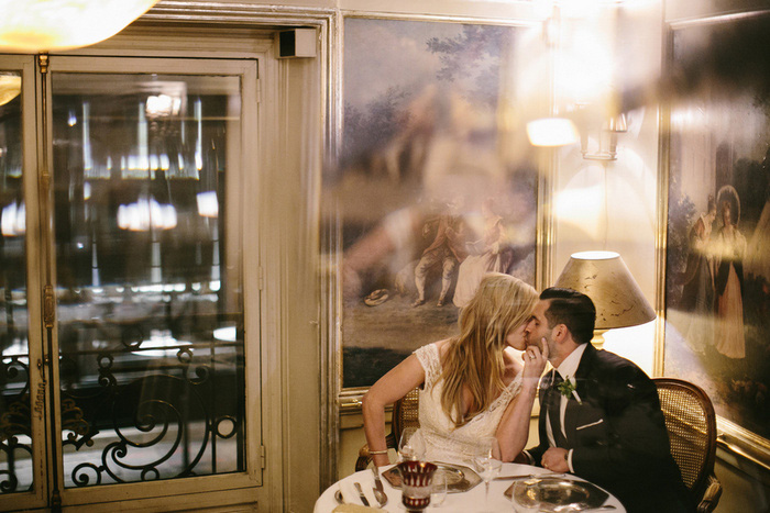 bride and groom kissing in Paris bistro